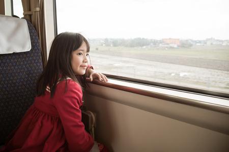 Niña asiática mirando por la ventana. Ella viaja en un tren, el filtro de la vendimia