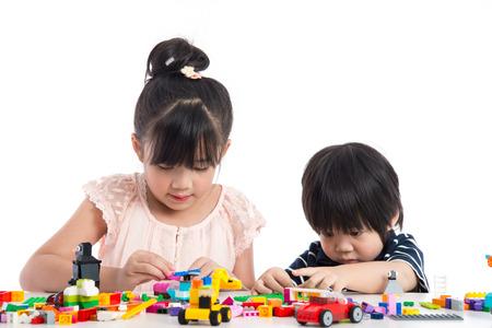 分離した白地にカラフルな構造のブロックで遊ぶ小さなアジア子供たち 写真素材