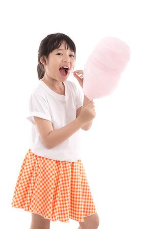 caramelos: Muchacha asi�tica linda que sostiene rosa de algod�n de az�car en el fondo blanco aislado Foto de archivo