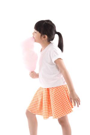 algodon de azucar: Muchacha asiática linda que sostiene rosa de algodón de azúcar en el fondo blanco aislado Foto de archivo