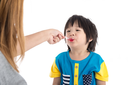 Asian Mother giving her son syrup because of the flu,on white background isolated