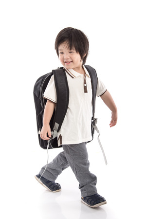 Portrait of Asian schoolboy with backpack walking isolated on white photo