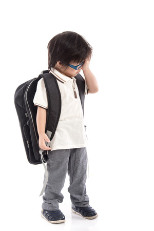 comfortableness: Portrait of Asian schoolboy with backpack wearing glasses isolated on white