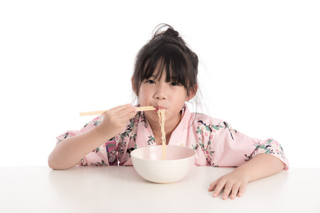eating noodles: Little asian girl wearing kimono and eating noodles on white background isolated Stock Photo