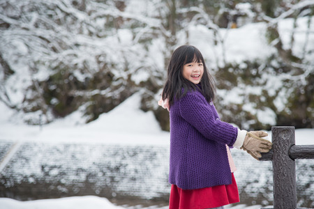 Cute asian girl smiling outdoors in snow on cold winter day photo