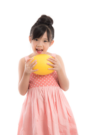 Little asian girl holding melon on white background isolated photo