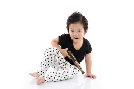 antique asian: Cute asian boy sitting  and holding toy antique gun on white background isolated Stock Photo