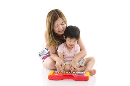 Lindo madre enseña a su hijo hijo a tocar el piano de juguete eléctrico en el fondo blanco aislado