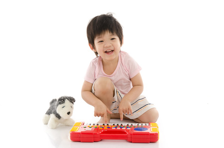 Little asian boy playing electrical toy piano on white background isolated photo