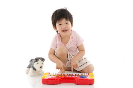 piano: Niño asiático que juega el piano de juguete eléctrico en el fondo blanco aislado