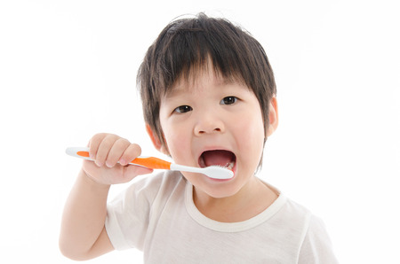 white teeth: Cute asian bay brushing teeth on white background isolated Stock Photo