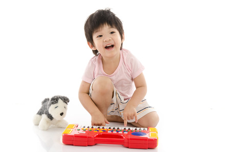 asian art: Little asian boy playing electrical toy piano on white background isolated Stock Photo