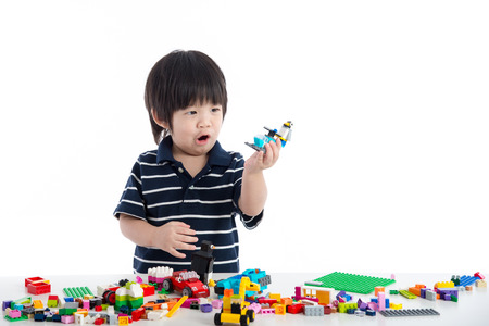 Little asian child playing with colorful construction blocks on white background isolated Stock Photo