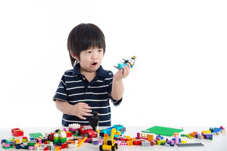 enfant qui joue: Petit enfant asiatique jouant avec des blocs de construction colorés sur fond blanc isolé