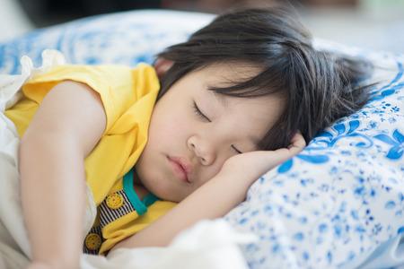 enfant malade: Mignon bébé qui dort sur le lit asiatique