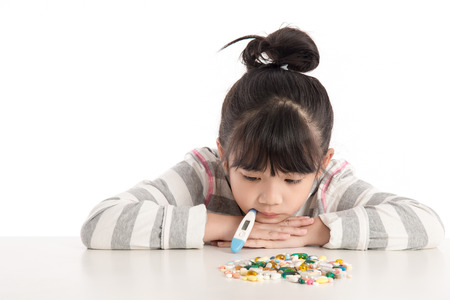 Sick girl looking pills on white table,isolated