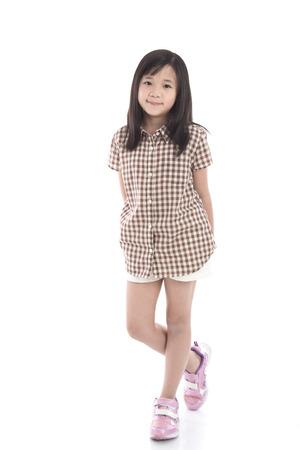 分離した白い背景の上に立って美しいアジアの少女