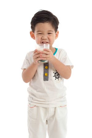 Cute asian boy drinking milk on white background isolated