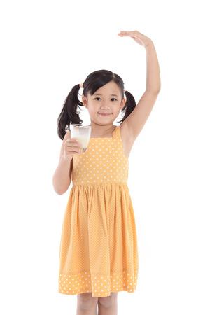 かわいいアジアの子分離した白い背景の上に牛乳を飲む 写真素材