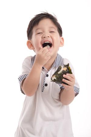 niños desayunando: Niño asiático lindo comer bolas de arroz o onigiri en segundo plano blanco aislado Foto de archivo