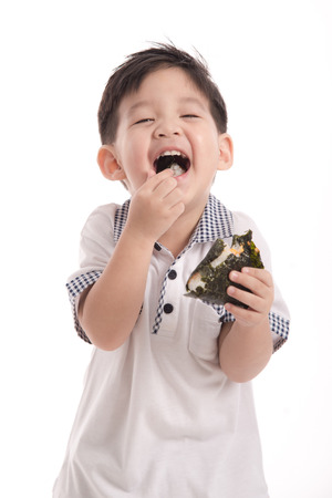 Schattig Aziatisch kind het eten van rijst bal of onigiri op witte achtergrond geïsoleerde Stockfoto