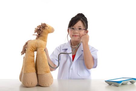 bebe enfermo: Niña que juega a un médico aislado en fondo blanco Foto de archivo