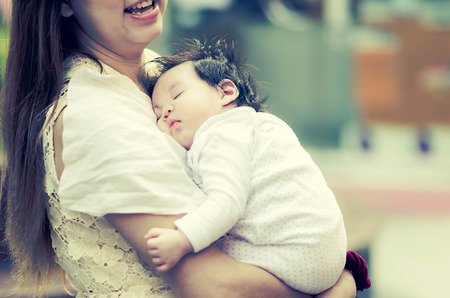 asian toddler: Young Asian mother hugging her baby outdoors,vintage filter