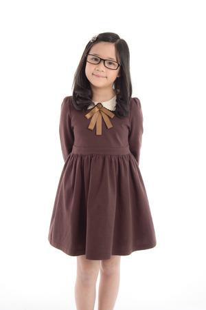分離した白い背景の上に制服を着る美しいアジアの少女の肖像画 写真素材