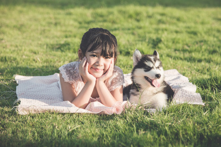 husky: Beautiful asian girl lying on green grass with a siberian husky puppy,Vintage filter