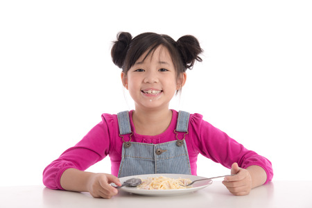 分離した白い背景のスパゲッティ カルボナーラを食べるかわいいアジアの女の子