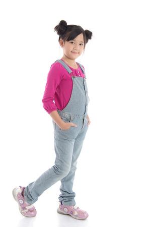 分離された白地のオーバー オールで美しいアジアの少女の肖像画 写真素材