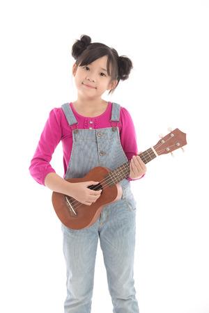 Cute asian girl holding ukulele on white background isolated
