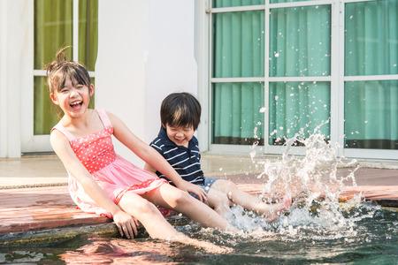 riendo: Ni�os asi�ticos chapoteando en la piscina