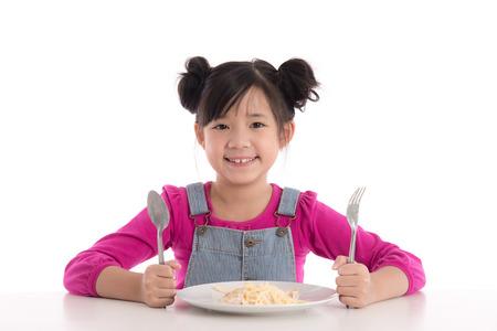 Ragazza asiatica sveglia che mangia spaghetti Carbonara su fondo bianco isolato