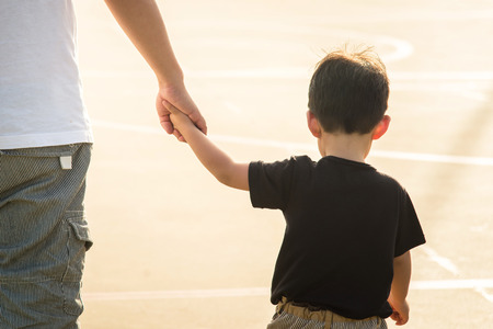 Father's hand lead his child son under sun light, trust family concept Banque d'images