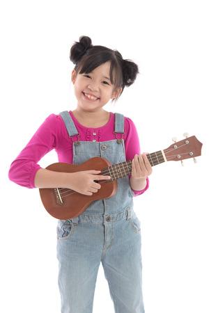 nene y nena: Muchacha asi�tica linda que sostiene ukelele en el fondo blanco aislado