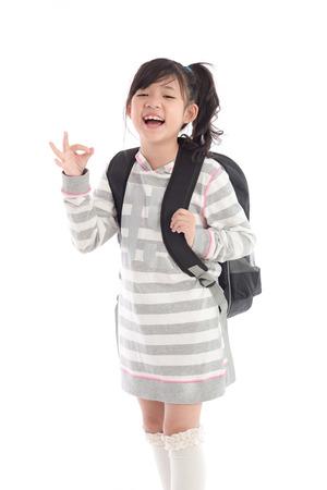 uniforme escolar: Ni�a de la escuela asi�tica hermosa con el morral que muestra la muestra aceptable en el fondo blanco aislado