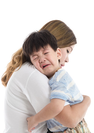 Asian mother comforting her crying child on white background isolated Stock Photo