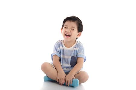 niños sentados: Muchacho asiático feliz que se sienta en el fondo blanco aislado