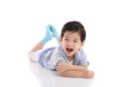 Cute asian boy lying on white background isolated Imagens