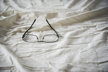 bedsheets: Modern Glasses on white bed in the morning sunday for background Stock Photo