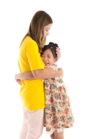 Asian Mother embracing and consoling daughter on white background iisolated Stock Photo