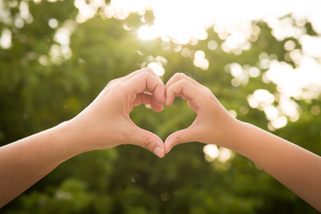 heart hands: Mother and her child holding hands in heart shape framing on nature background