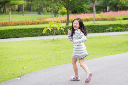 Happy asian girl running in the park