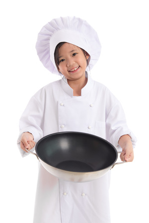 pan asian: Little asian girl in chef uniform holding the frying pan,isolated on white