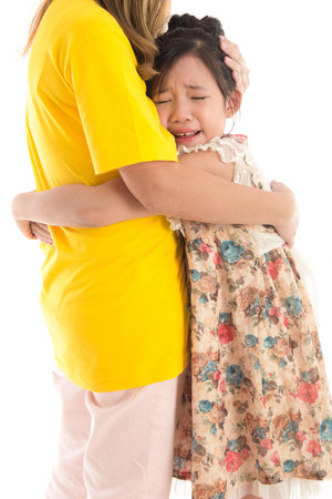 soothe: Asian Mother embracing and consoling daughter on white background iisolated Stock Photo