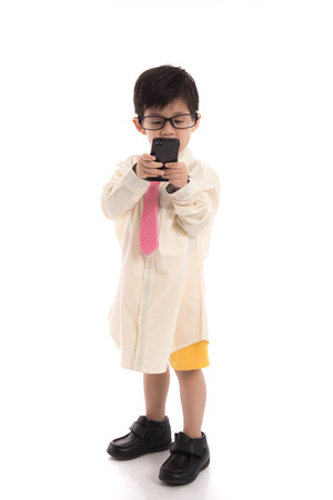 pretending: Little asian child pretending to be  businessman using smart phone on white background isolated