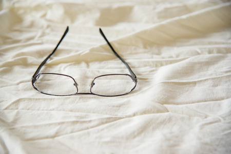 bedsheets: Modern Glasses on white bed in the morning sundayfor background Stock Photo