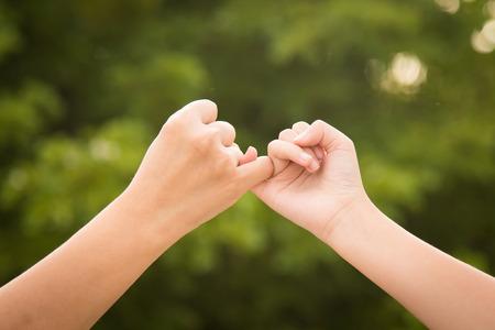 dedo meÑique: Madre e hija que hacen una promesa del meñique en el fondo la naturaleza