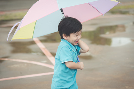 Happy asian boy holding colorful umbrella playing in the park,vintage filter